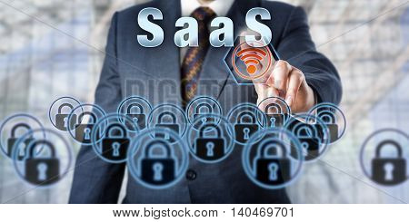 Manager pressing SaaS on an interactive touch screen interface. Business services delivery metaphor. Information technology concept for Software as a Service and service-oriented business computing.