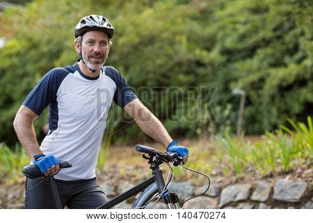 Smiling man standing with mountain bike on the road