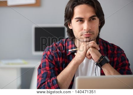 Let me think. Pleasant delighted thoughtful man sitting at the table and holding pencil while thinking poster