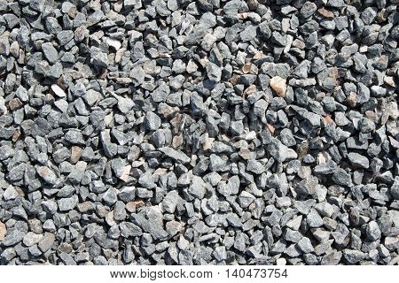 Background composed of crushed gravel fine fraction in sunlight