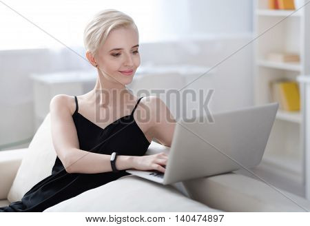 Working in a good mood. Contented pretty woman working on her laptop while sitting on the couch at home