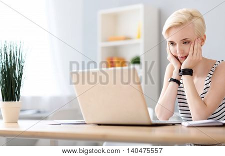 So happy to see you. Pleasant amiable woman chatting on the laptop while sitting at the table and holding her head on her hands