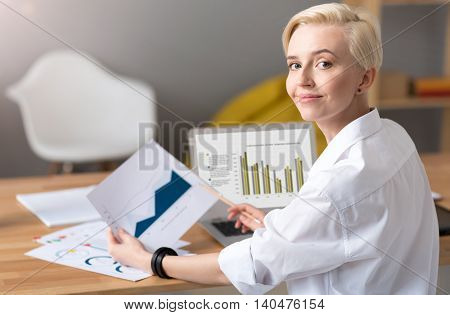 I am good at it. Woman looking at the camera while sitting at the table with the laptop and analyzing charts