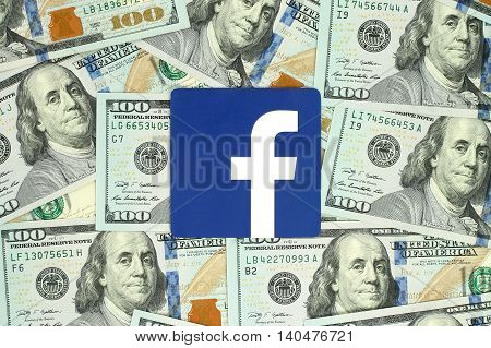 Kiev, Ukraine - June 13, 2016: Facebook logo sign printed on paper and placed on money background. Facebook is a well-known social networking service.