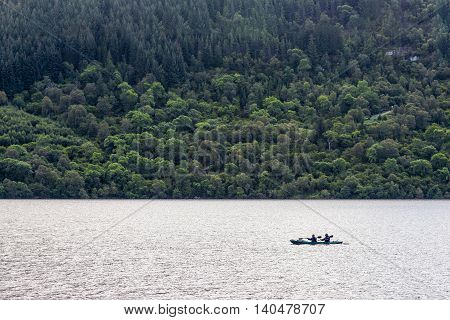 Loch Ness, United Kingdom - August 19, 2014: View of two canoeists in early morning. loch Ness is a large, deep, loch in the Highlands extending for approximately 37 km southwest of Inverness.