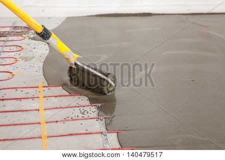 Electric floor heating system installation in new house. Worker align cement with roller