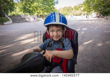 Little boy smiling in the seat bicycle. Kid has biking helmet. Protection on the bicycle.