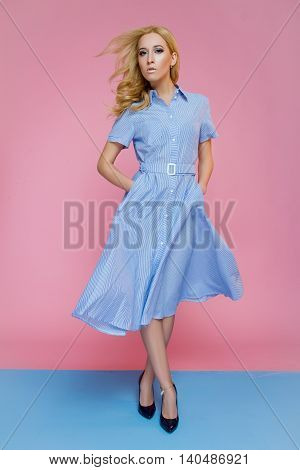 Girl in a fashionable summer dress on a pink and blue background confidently striding forward . Hair develops wind .