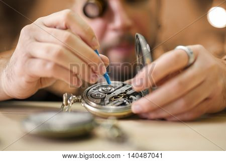 Close up portrait of a watchmaker at work. He is wearing specialist magnifying glass.Old pocket watch being repaired by watch maker.
