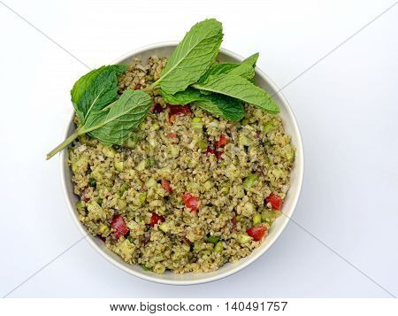 Tabouleh: Bulgur wheat salad in a white bowl with a sprig of mint shown on a white background.