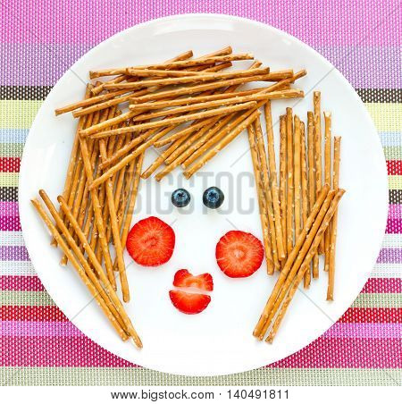 Edible picture on the plate - cute girl face of berries and cookie straws for breakfast for children. Fun food art idea for positive food top view