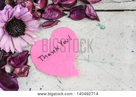 Thank you note in heart shape paper with pink flowers and purple petal on grungy white wooden table