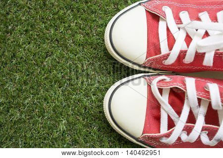 Red shoes on green grass background. Copy space.