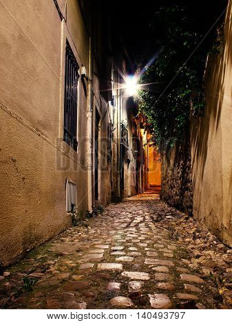 an old small alley at night with streetlamps