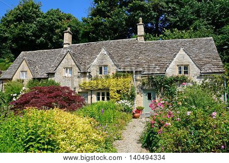 Pretty Cotswold cottages and gardens during the Summertime Bibury Cotswolds Gloucestershire England UK Western Europe.