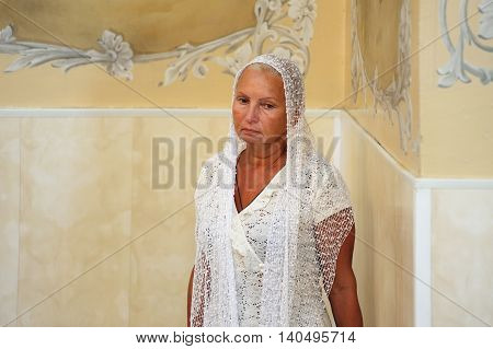 Orel Russia - July 28 2016: Russia baptism anniversary Divine Liturgy. Single senior tanned woman in kerchief in church horizontal