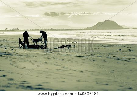 Hazy evening light sillhouette Long line fishermen monochromatic setting up equipment and torpedo on Papamoa beach with landmark Mount maunganui on horizon.
