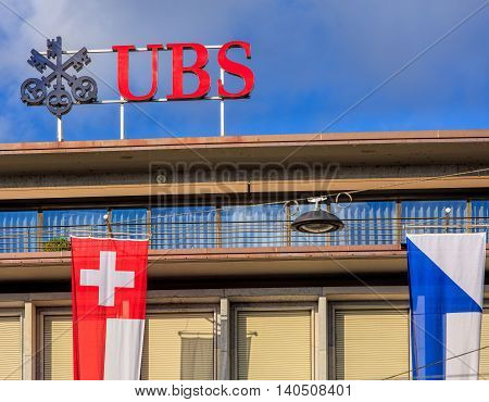 Zurich, Switzerland - 30 July, 2016: upper part of the UBS building on Paradeplatz square, decorated with flags of Switzerland and Zurich. UBS AG is a Swiss global financial services company.