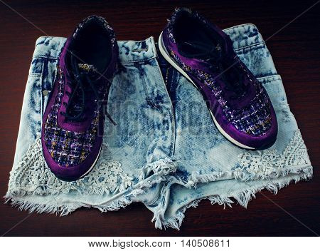 stylish sneakers and denim shorts over wooden background