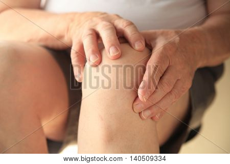 Older man has both hands on his sore knee.
