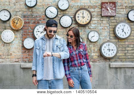 Cheerful couple is standing near wall with varied old clocks. Man is raising hand and looking at his watch with interest. Woman is smiling