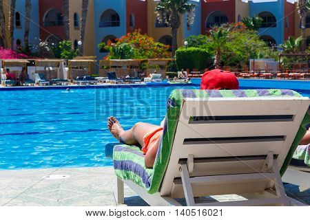 Sunbathing by the hotel tourist resort swimming pool man lying down on a sunlounger looking over the water