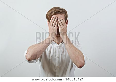 Young Adult Male Wearing White Shirt Covers His Face by Both Hands, Gesturing He Has Made a Big Mistake