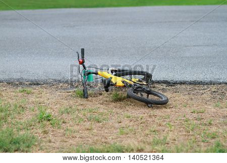 Yellow bike fell off beside the street