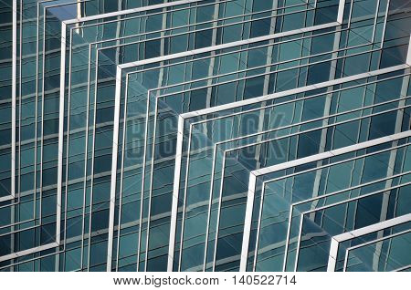 Glass office window reflecting blue tones of the sky
