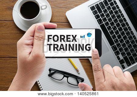 FOREX TRAINING message on hand holding to touch a phone top view table computer coffee and book