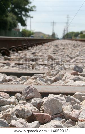 Rocks on the train tracks, with a vanishing point in the distance