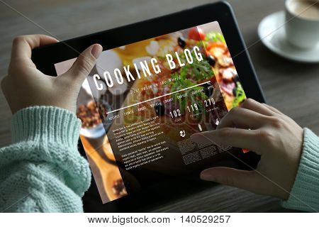 Female hands with tablet. Cooking blog concept