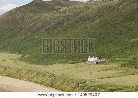 An image of a beachside cottage in solitude shot at Rhossili Bay South Wales UK