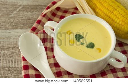 Closeup Cream corn soup on a wooden table.
