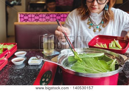 Asian women eating healthy vegetables happily. select Focus your chopsticks and vegetables