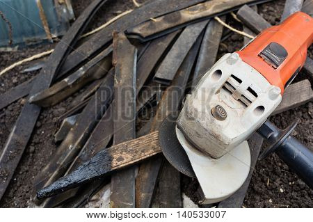 Angle grinder used on construction site for cutting wooden laths whetstones debris. Tools and laths on a workplace