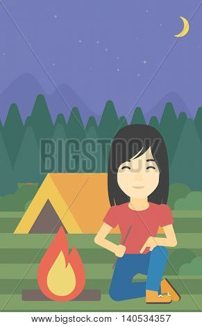 An asian woman kindling campfire on the background of camping site with tent. Tourist relaxing near campfire. Woman sitting near campfire. Vector flat design illustration. Vertical layout.