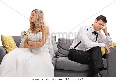 Newlywed coupe sitting on a sofa angry at each other in a middle of an argument isolated on white background