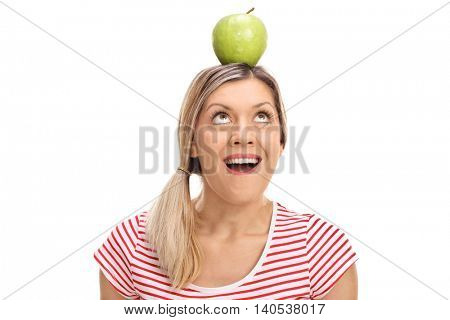 Young blond woman balancing an apple on her head isolated on white background