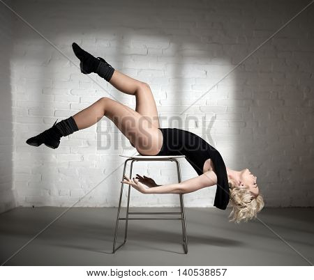 Young female dancer practicing in a beautiful pose, lying on chair. Side view.