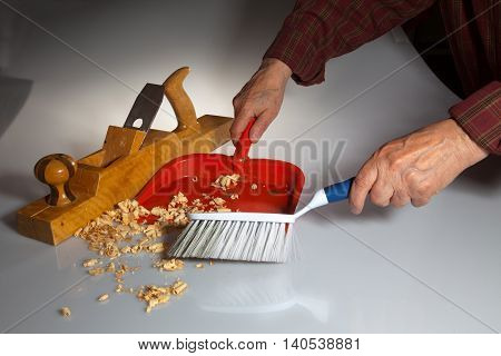 Hands of an old man clean up wooden chips from white surface with brush and dustpan after working with wooden planer (joiner).