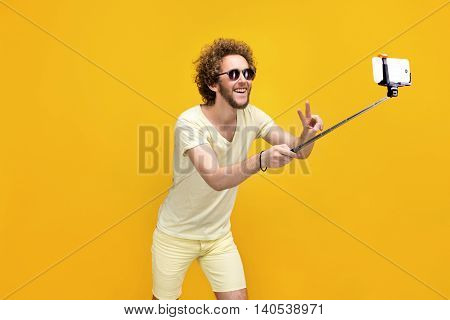 Portrait of young man in sun glasses taking selfie using monopad.Studio shot.Yellow background.Isolate.