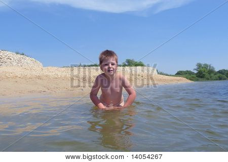 Tanned Boy On A Beach Awash In Water