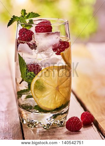 Alcohol drink. On wooden boards is glass with alcohol drink and ice cubes. A drink three hundred two cocktail raspberry mojito and some slice lime with mint. Country life. Outdoor. Light background.