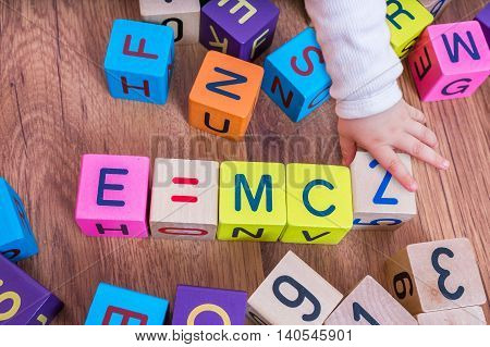 Genius baby with high IQ is playing with cubes and writing formulas.
