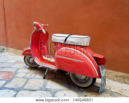 CORFU-AUGUST 22: Vintage Vespa scooter parked on Kerkyra street on August 22 2014 on Corfu island. Greece. Vespa is an Italian brand of scooter manufactured by Piaggio.