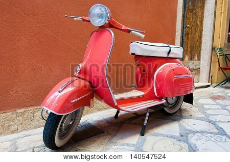 CORFU-AUGUST 22: Classic Vespa scooter parked on Kerkyra street on August 22 2014 on Corfu island. Greece. Vespa is an Italian brand of scooter manufactured by Piaggio.