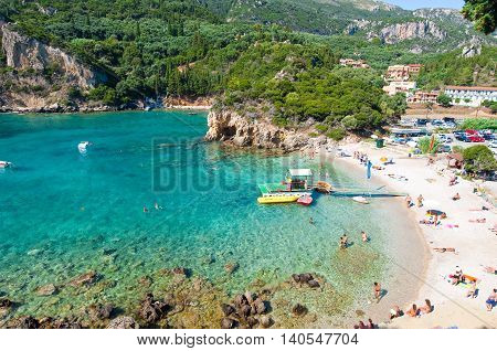 CORFU-AUGUST 26: Palaiokastritsa beach people sunbathe on the beach on August 262014 Corfu island Greece. Palaiokastritsa is a village with famous beaches in the North West of Corfu.