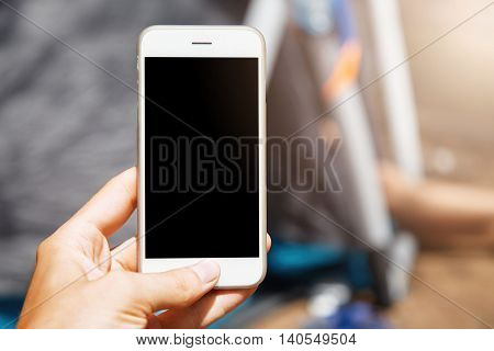 Beautiful Close-up Shot Of Modern White Smartphone On Blur Background. Woman Holding Her Up-to-date
