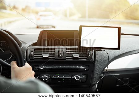 Nice close-up shot of modern car interior. Young male driver with hands on steering wheel. Good view of long road with transport. Laconic design of dashboard. Travelling by automobile concept.